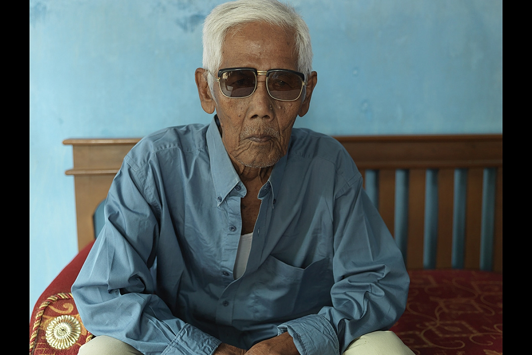Bapak Saih bin Sakam, born 16 April 1923, the only living survivor of the massacre: `We were shot from the back, from a distance of about 2,5 meters. The man behind me was shot dead, the bullit went right through his body and hit my back. The man fell upon me and I felt his blood running over my face. When they left they shot again every body, to be sure we were all dead. They shot me through my hand. I was one of fourteen men who survived. My father, who was in the same line as I, was killed`.